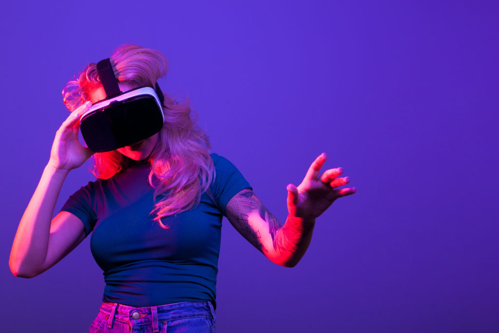Woman wearing virtual reality goggles on blue background in studio photo. Conceptual colored image